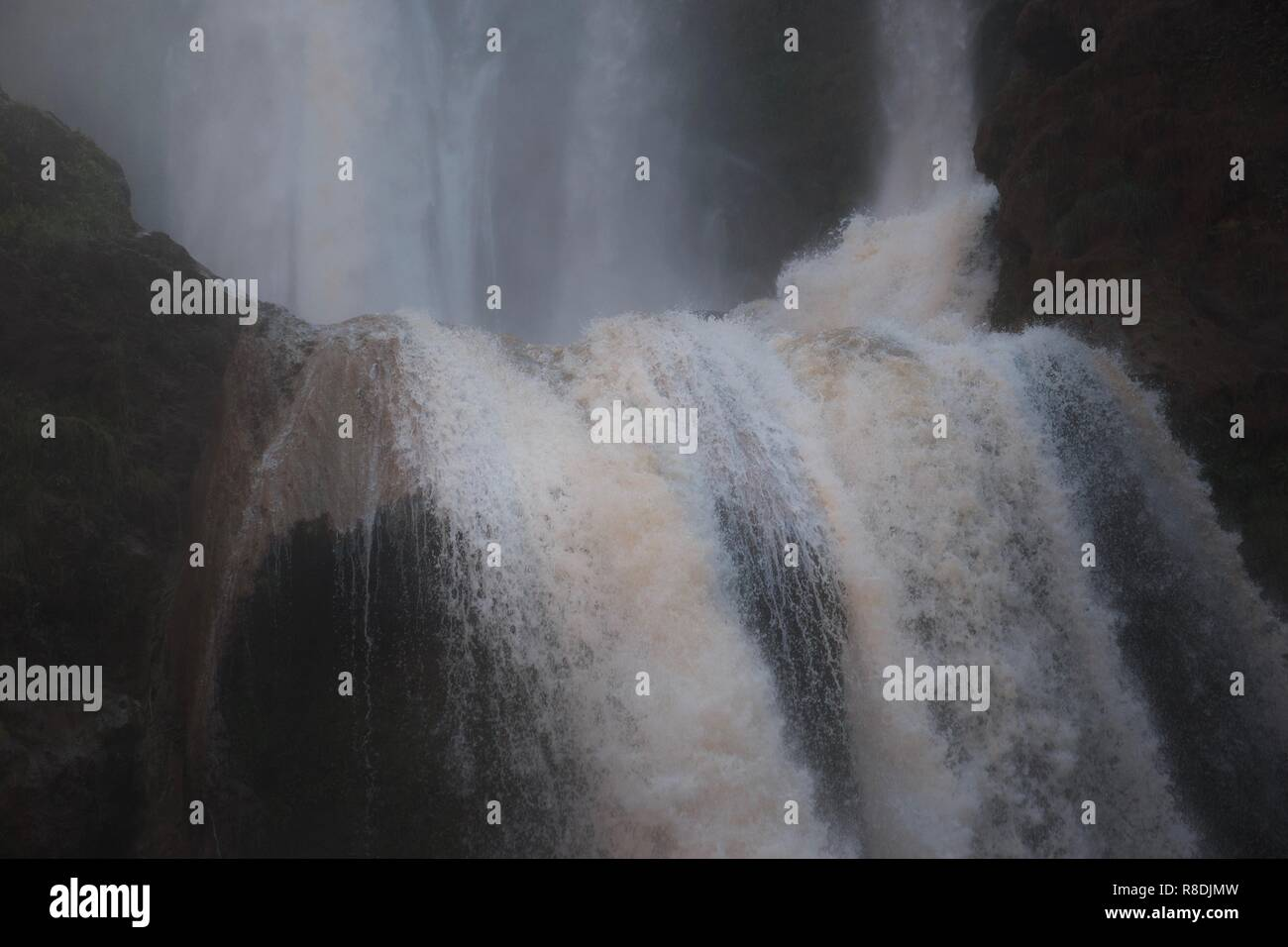 Close up of violently foaming water plunging off the edge of a dramatic waterfall, the top half of which is in the background - Stock Image