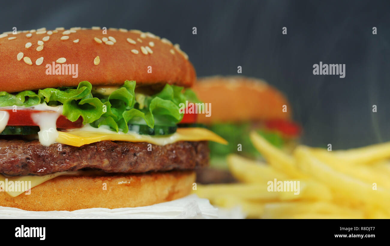 Big appetizing burger with meat cutlet, vegetables, cheese, lettuce and sauce. Hamburger rotates on other meal background, close-up view. Unhealthy yu - Stock Image