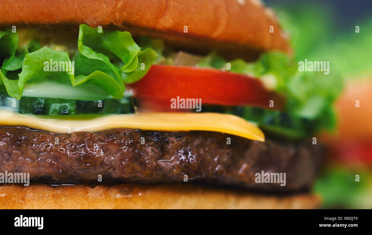 Macro detailed view of juicy beef burger layers. Cutlet, onion, vegetables, melted cheese, lettuce, sauce and topped sesame seeds. Hamburger rotates.  - Stock Image