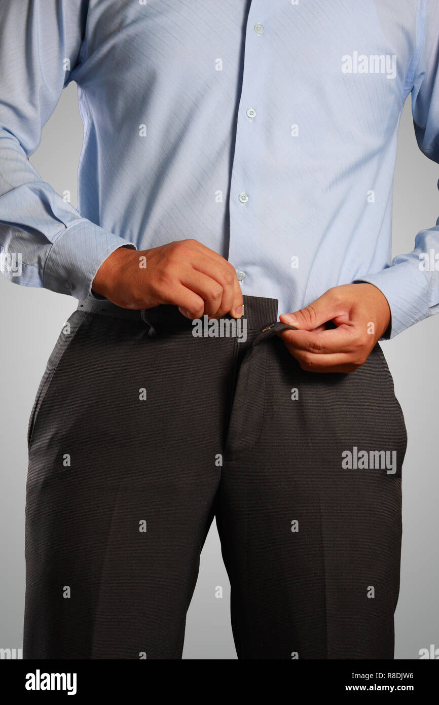 Photo image of a businessman dressing, pulling his pants placket. Closeup shot of male waist dressing, wearing a pants. Formal wear - Stock Image