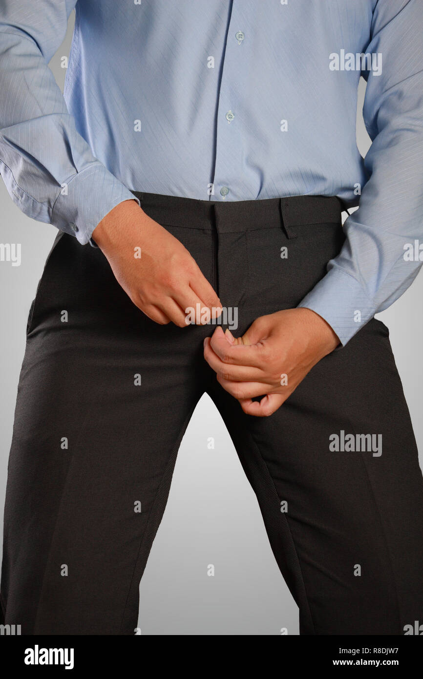 Photo image of a businessman dressing, pulling his pants zipper. Closeup shot of male waist dressing, wearing a pants. Formal wear - Stock Image