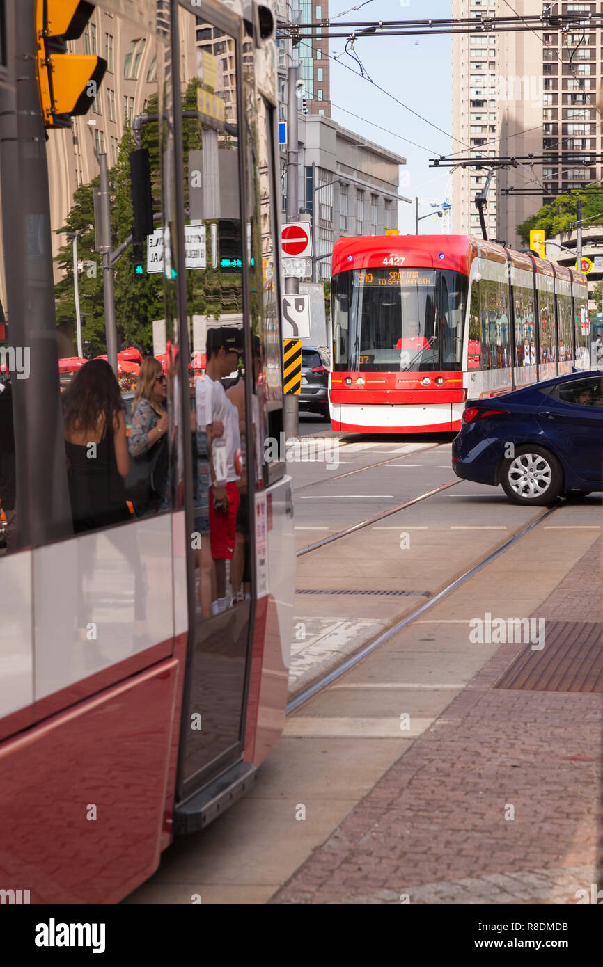 Flexity Outlook streetcars (number 4427) part of the Spadina line of the TTC (Toronto Transit Commission) running along Queens Quay W. City of Toronto - Stock Image