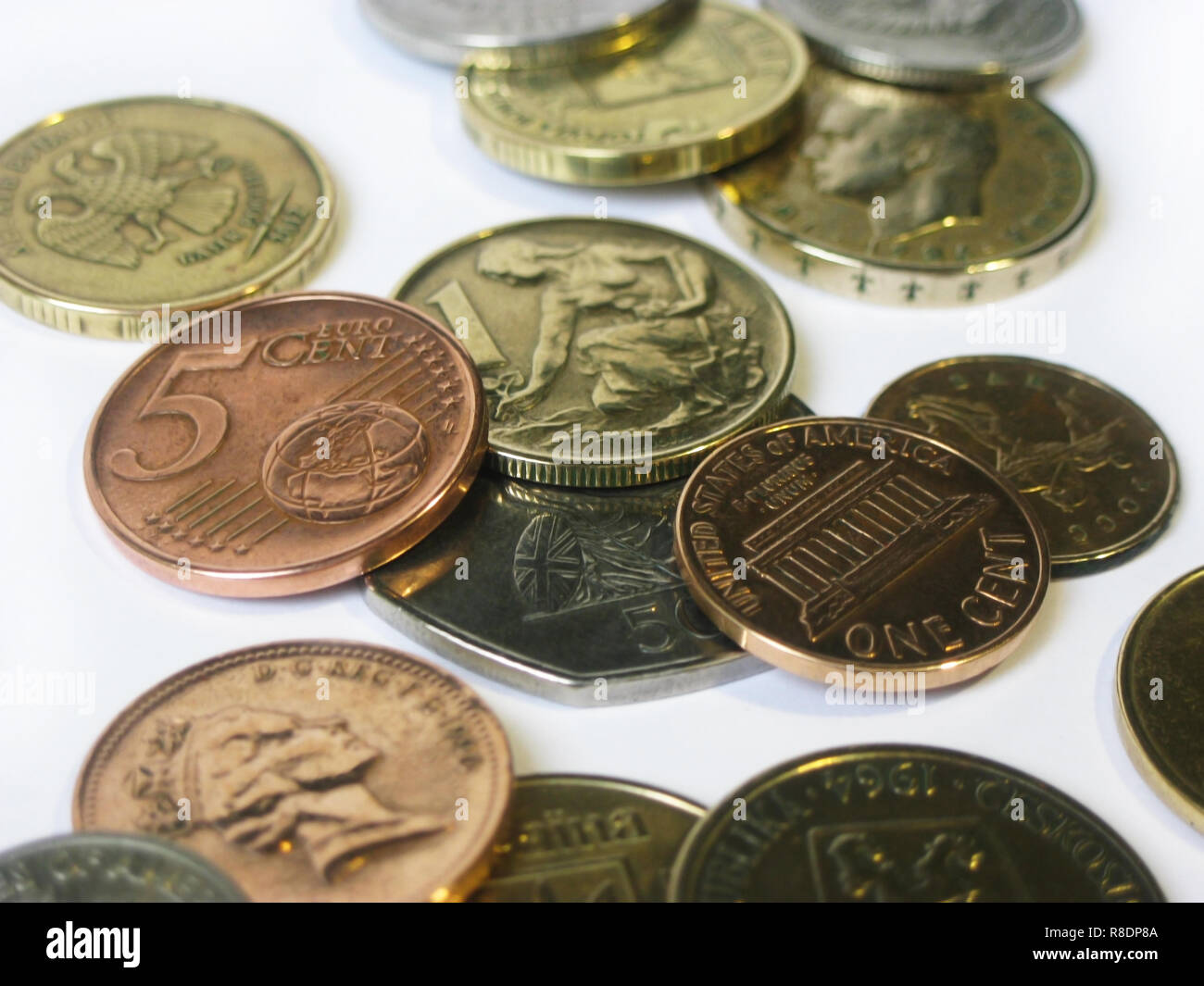 Different coins from various countries in macro on a white background - Stock Image