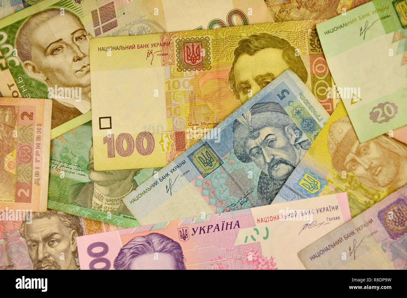 Many Ukrainian money bills of various denominations and colors. Ukrainian banknotes with portraits of historical and cultural figures and historical i - Stock Image