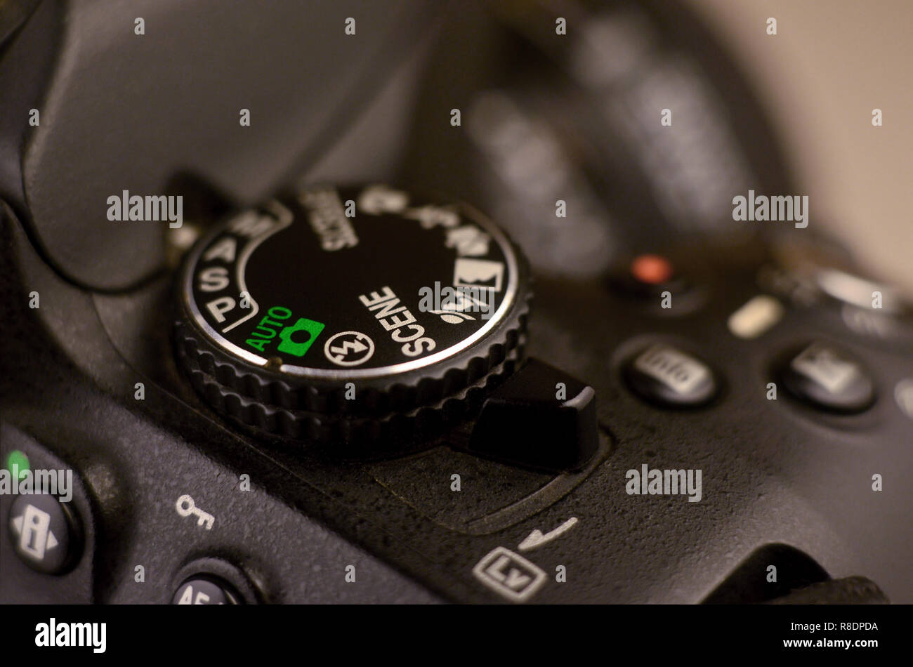 Close-up macro shot of a modern digital SLR camera. Detailed photo of black camera body with buttons to control and switch shooting modes - Stock Image