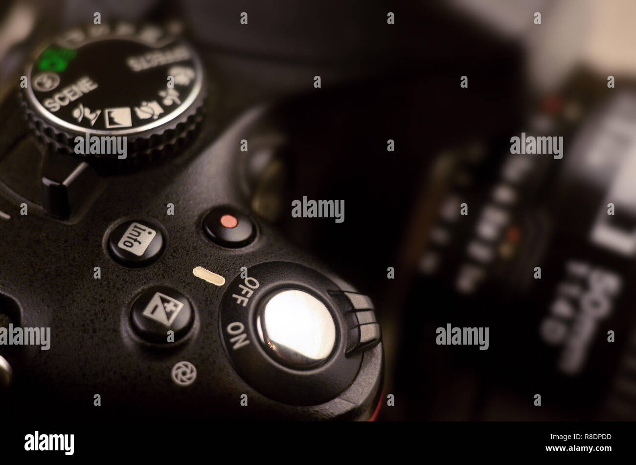 Close-up macro shot of a modern digital SLR camera. Detailed photo of black camera body with a classic wide aperture portrait lens - Stock Image