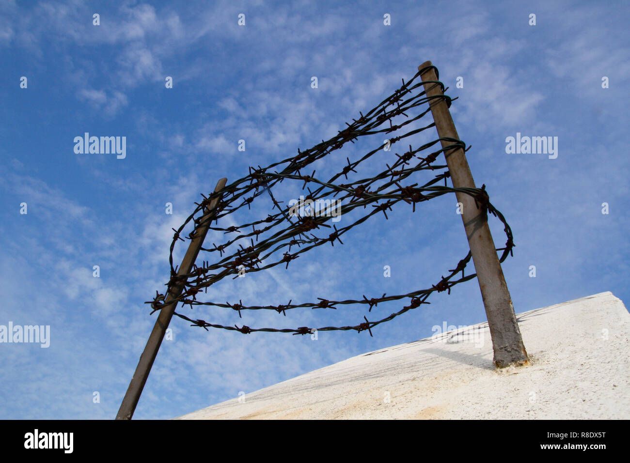 Barbed wire on the concrete fence against the blue sky. Captivity and deportation concept. Stock Photo