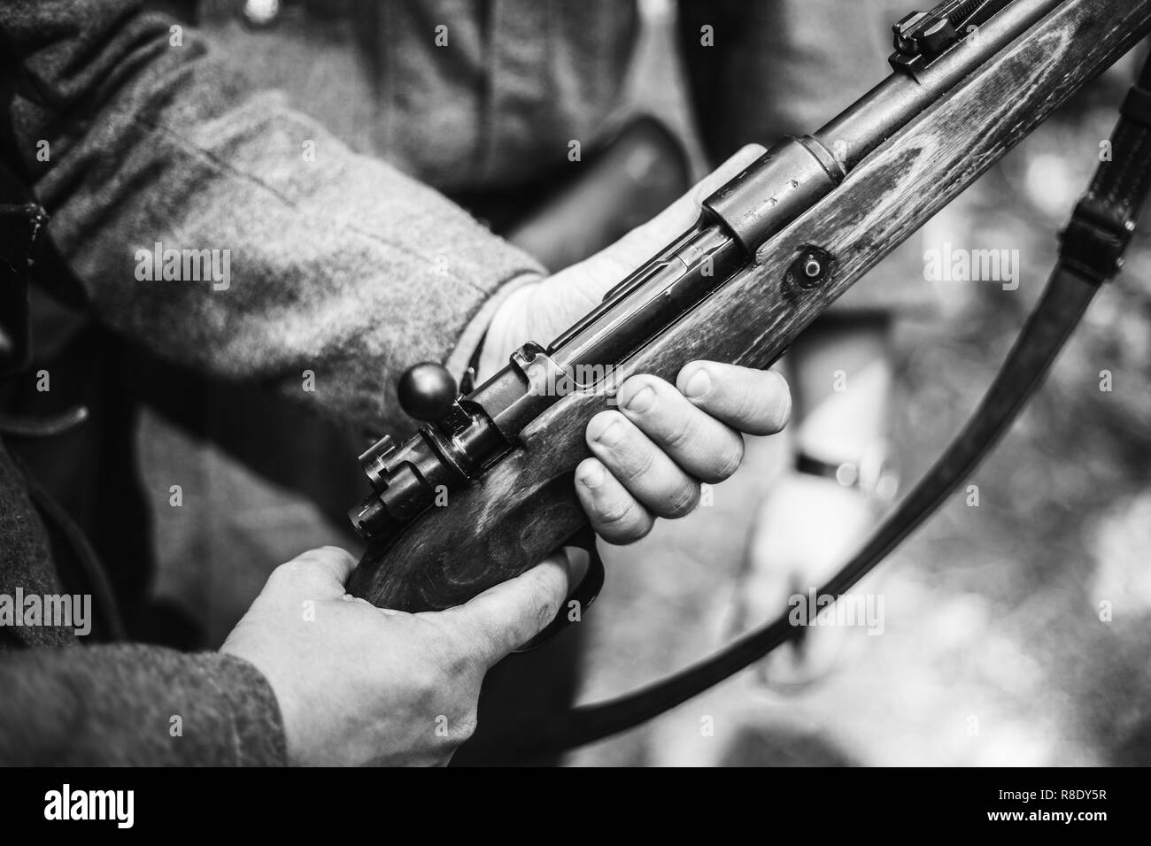 Re-enactor Dressed As World War II German Soldier Holding Rifle. Photo In Black And White Colors. Soldier Holding Weapon. German Military Ammunition O - Stock Image