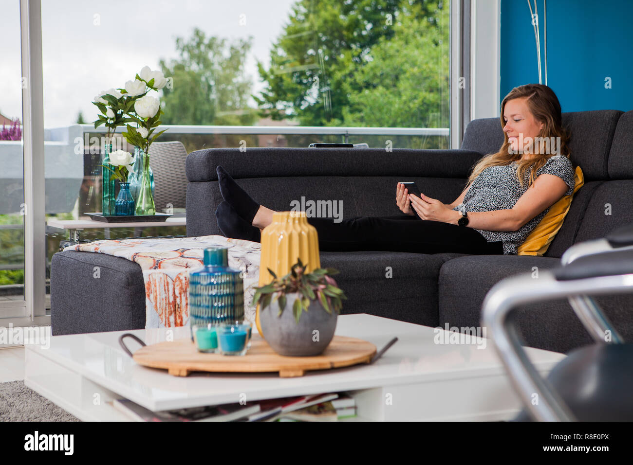 Young woman chilling on the couch reading an ebook - Stock Image