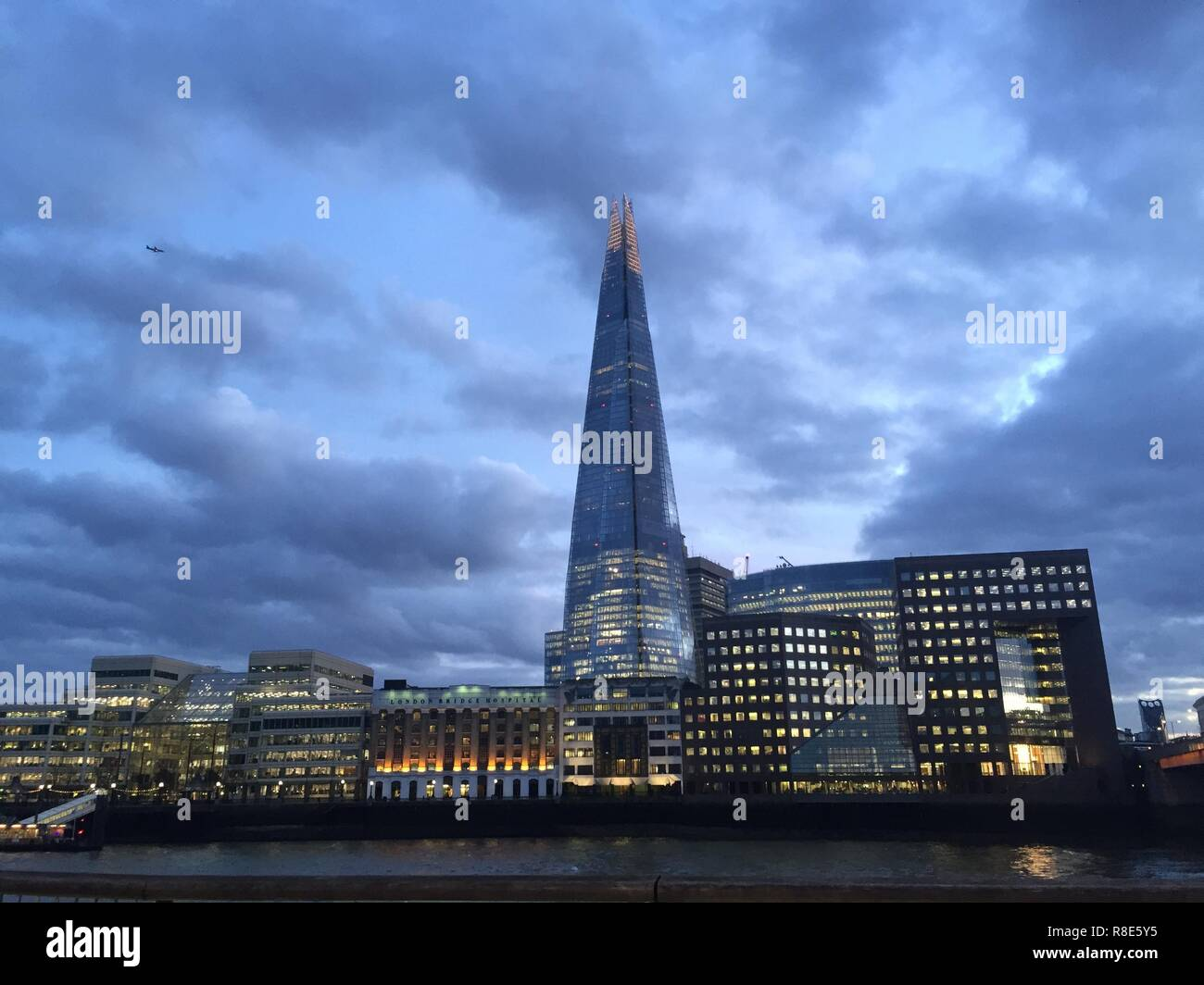 London England February 12 2018 The Famous Skyscraper At Dusk Across River Thames Illuminated By Interior Lights With Cloudy Sky Background
