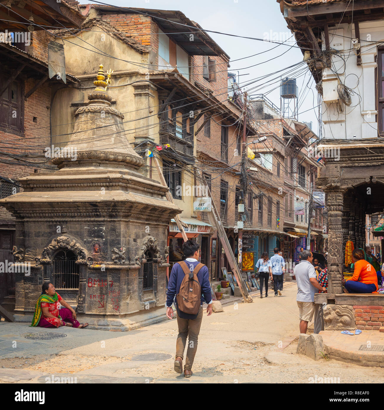 Young man walking past small temple and city street in Patan, Lalitpur,  Nepal. Stock Photo