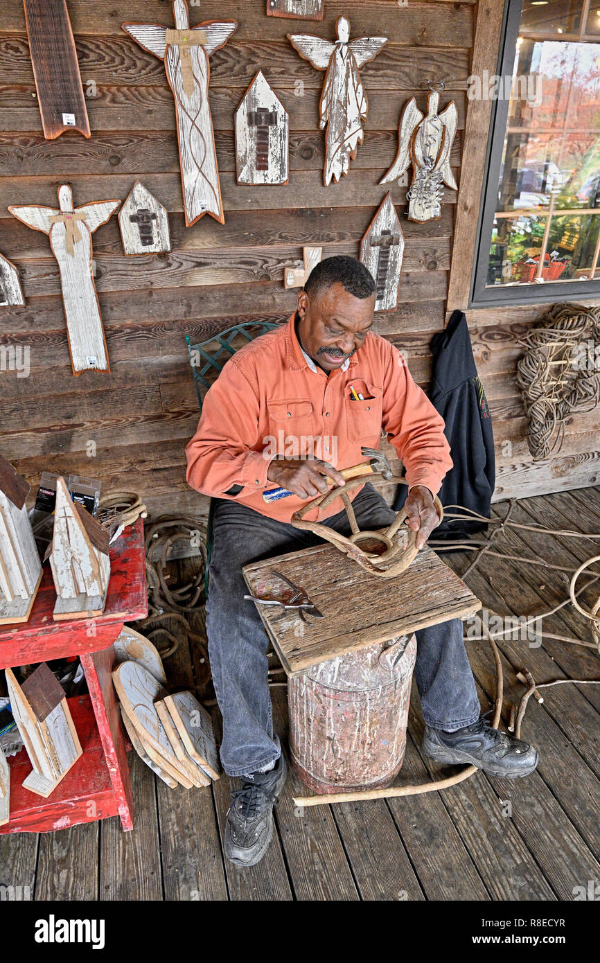 Black or African American woodworking artist making wooden figures and figurines for sale on the porch of Priester's Pecans near Fort Deposit Alabama. - Stock Image
