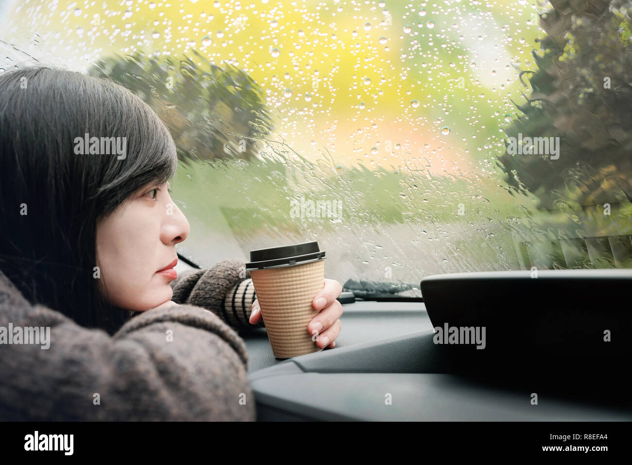 Rainy Day or Bad Weather in a Vacation Concept. a Sadness Woman with Hot Coffee sitting in Car and Looking Outside through Window, Waiting for Rain to - Stock Image