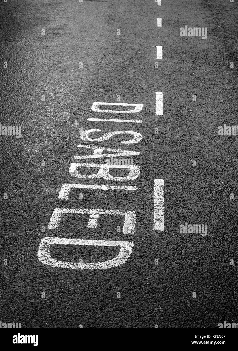 Disabled parking bay markings on a tarmac road - Stock Image