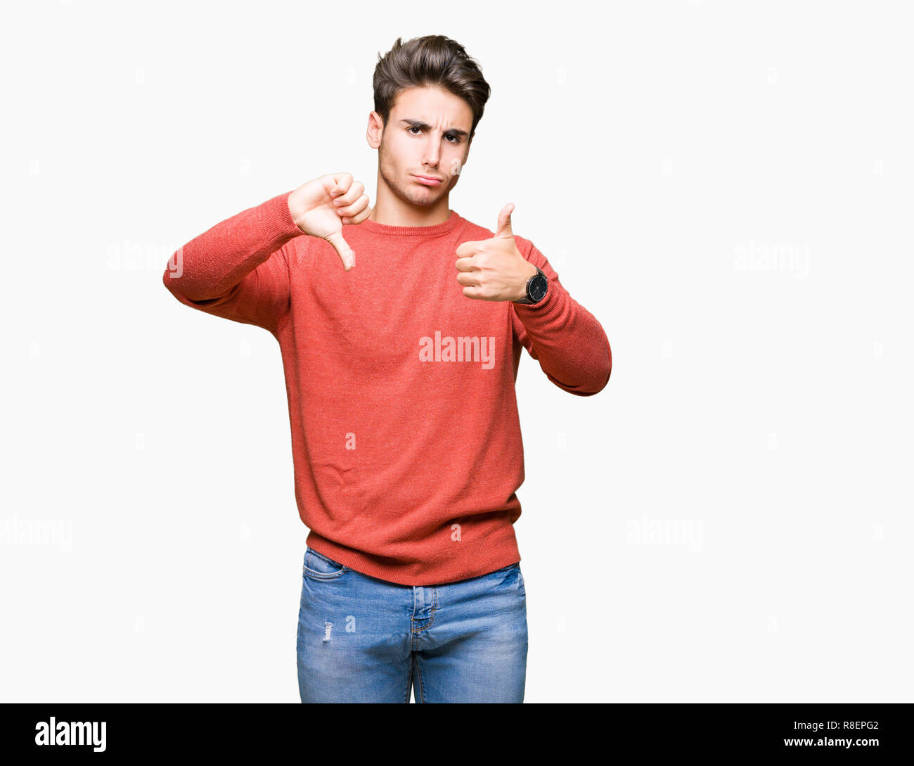 Young handsome man over isolated background Doing thumbs up and down, disagreement and agreement expression. Crazy conflict - Stock Image