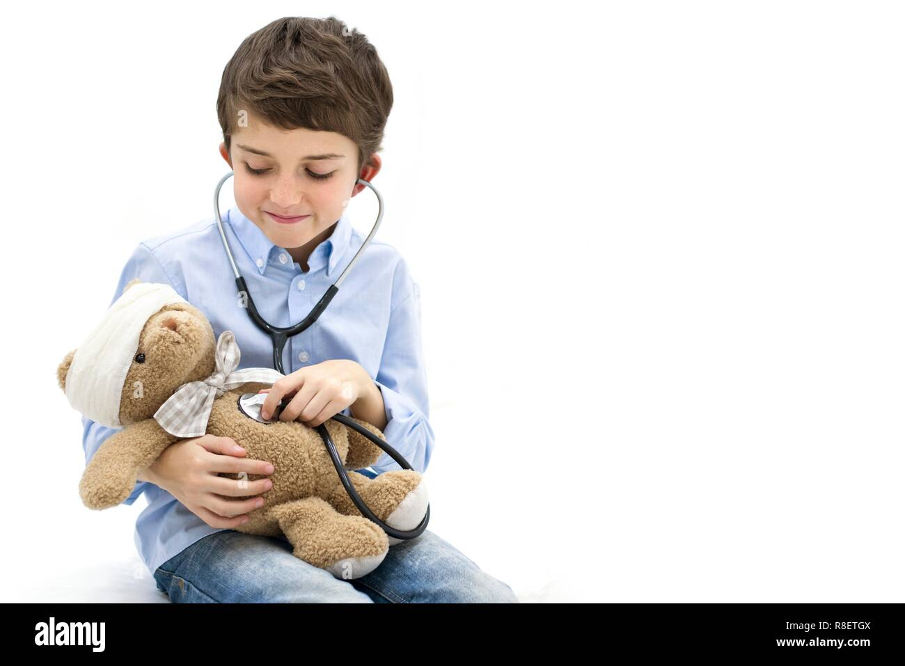 Boy role playing with teddy bear and stethoscope. - Stock Image