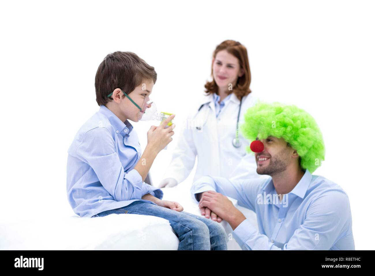 Boy using nebuliser with doctor dressed as clown. - Stock Image