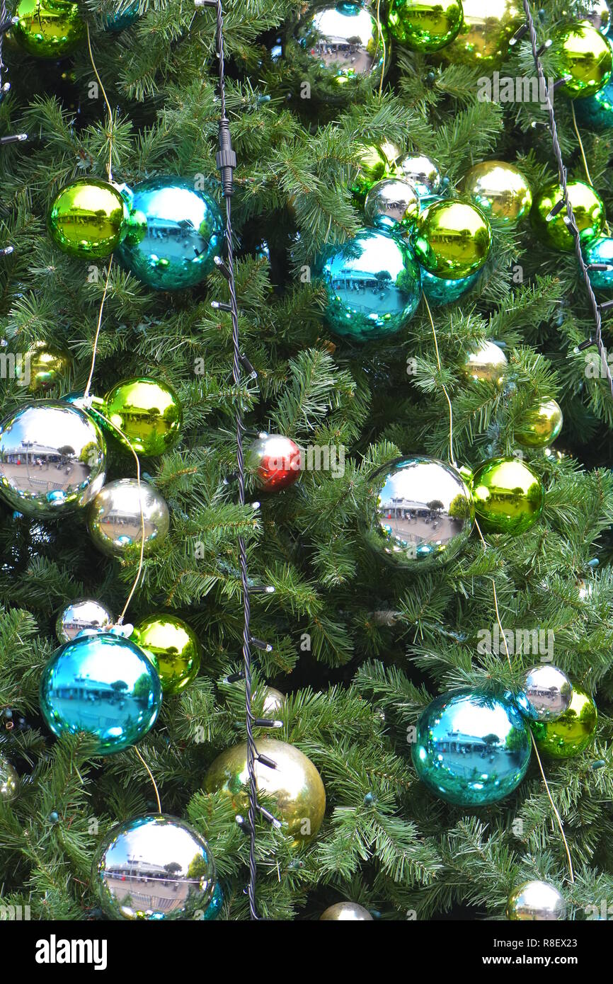 Detail of shiny Christmas decorations and LED lights on traditional conifer tree. - Stock Image