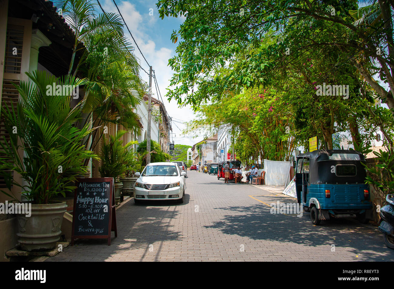 Streetscape in the old colonial dutch quarter, Galle Fort   Sunny scene with people relaxing, parked vehicles, lush greenery with blue cloudy sky. - Stock Image