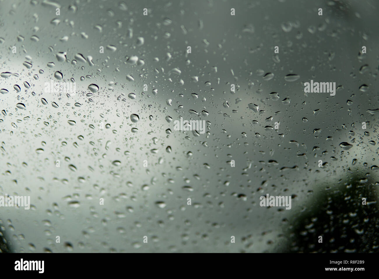 Rain drop on the car glass background.Road view through car window with rain drops, Driving in rain.Abstract traffic in raining day. View from car sea - Stock Image