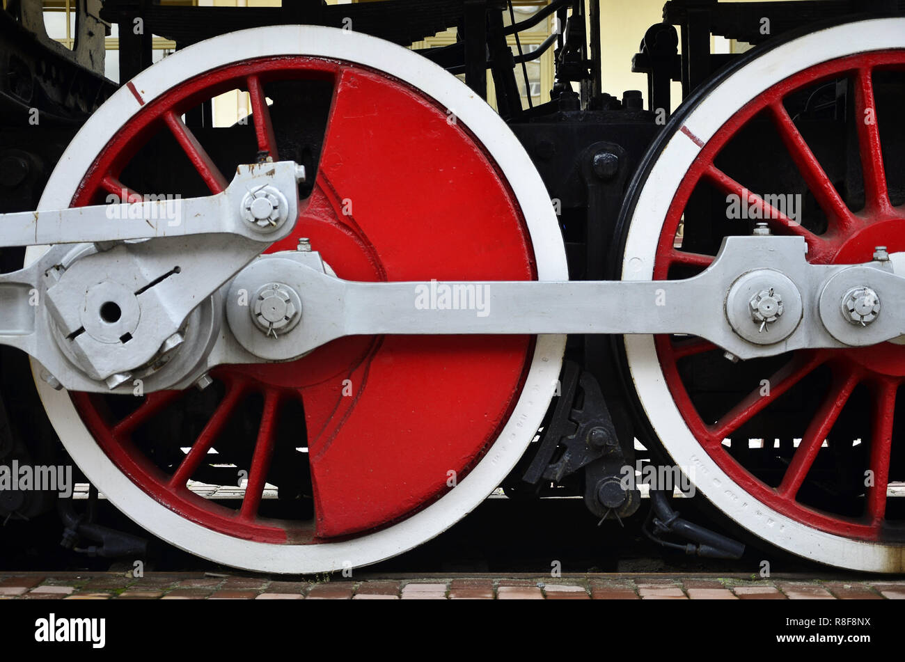 Red wheels of old USSR black steam locomotive. Wheels of an old soviet steam train Stock Photo