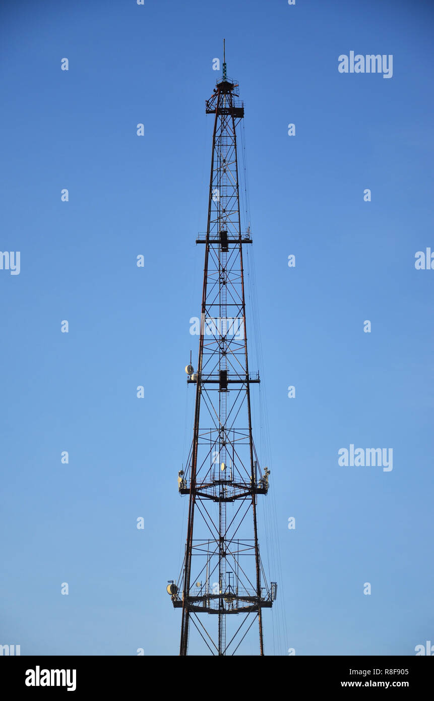 Radio communications tower against a blue cloudless sky. Abstract background associated with radio technologies, the mobile wireless communication - Stock Image