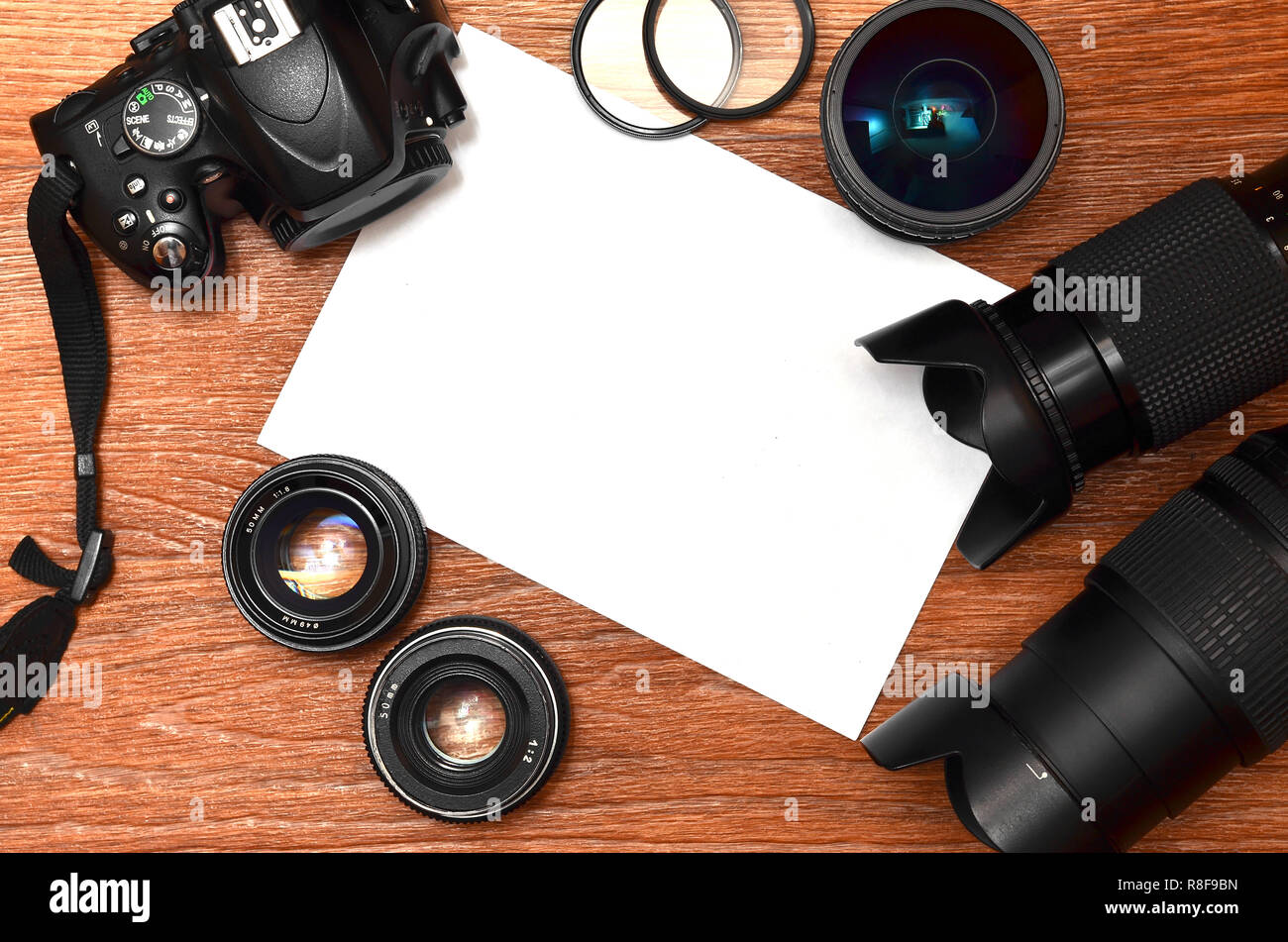Complete kit for modern digital SLR camera and blank sheet of paper for copyspace. The concept for learning photography. Cover for photo exhibitions,  - Stock Image
