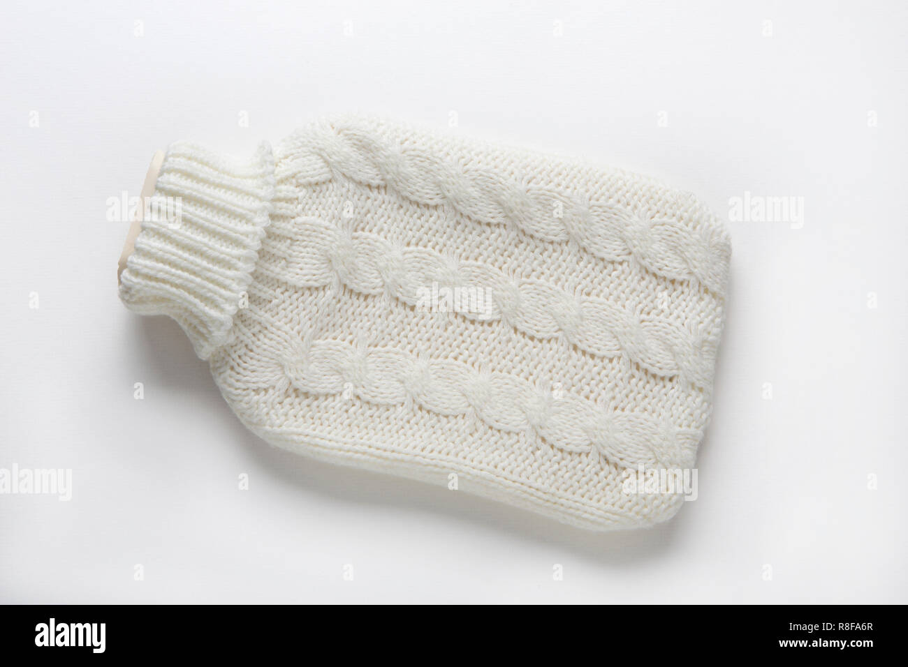 Hot water bottle in a knitted cover - Stock Image