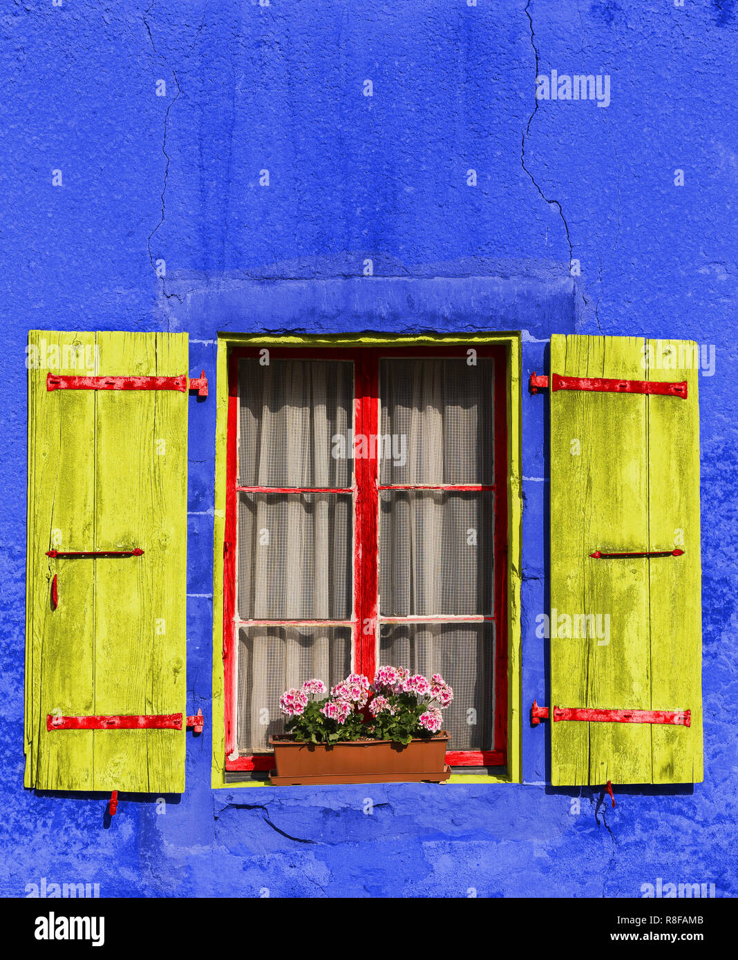 Beautiful old window with red flowers on the old rusty house. Blue facade. City of Nyon, canton Vaud Switzerland Stock Photo