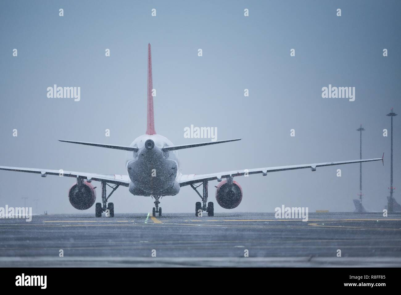 Winter day at the airport. Airplane taxiing to runway at snowing. - Stock Image