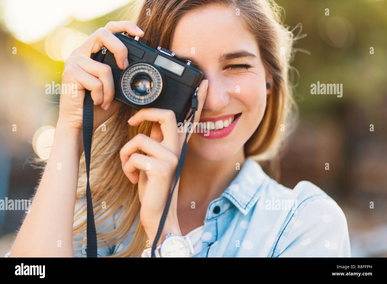 Pretty girl taking photos with a vintage camera on a sunny day, holding it near her eye, smiling. She wears blue sky denim shirt with white big dots a - Stock Image