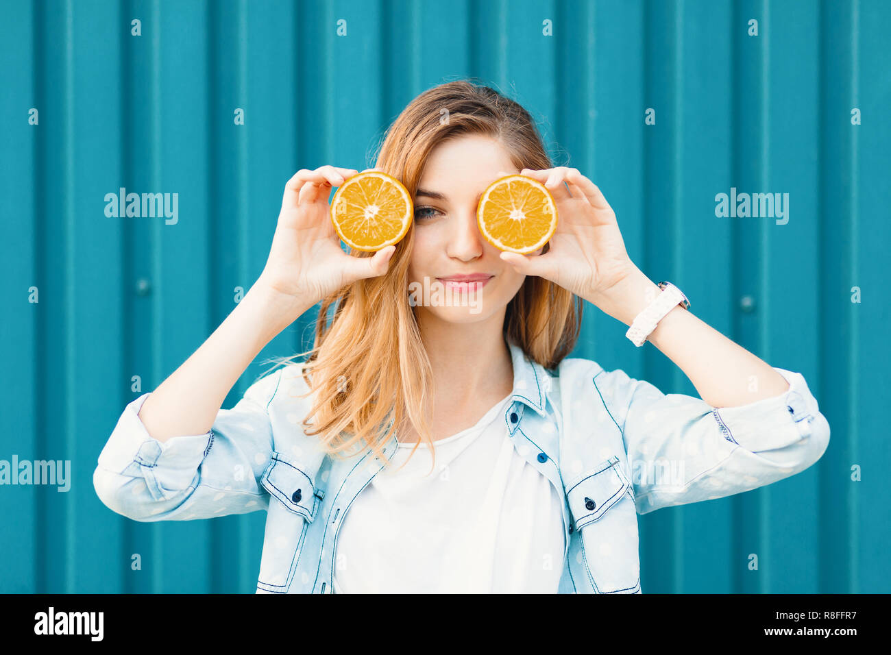 Carefree young beautiful girl using two halfs of oranges instead of glasses over her eyes over blue background. - Stock Image