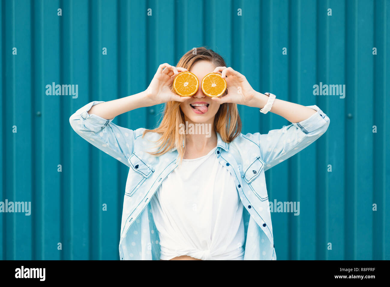 Carefree young beautiful girl using two halfs of oranges instead of glasses over her eyes, tongue out, over blue background. - Stock Image