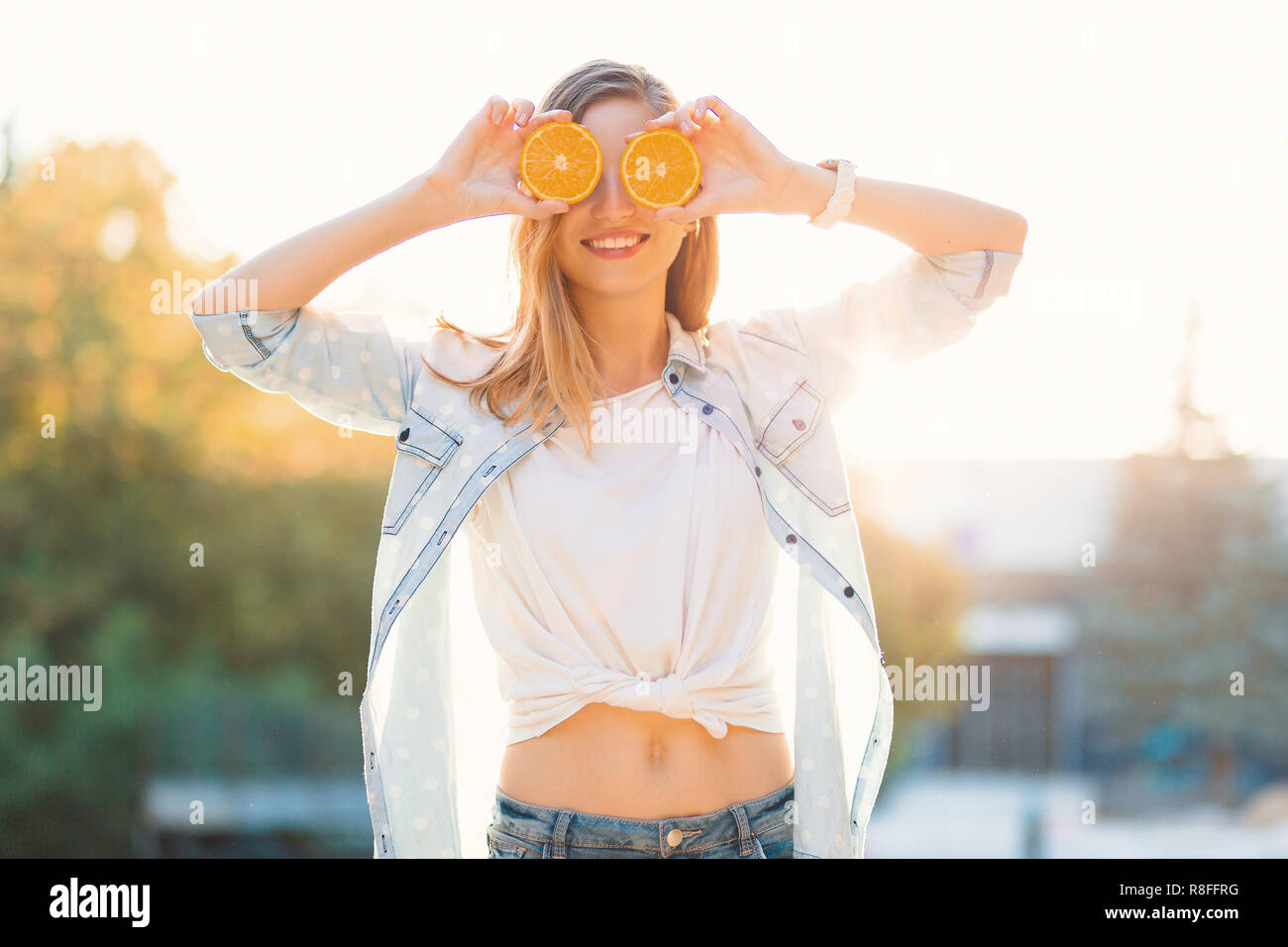 Carefree young beautiful girl using two halfs of oranges instead of glasses over her eyes, on a beautiful sunny day with sun rays in the background - Stock Image