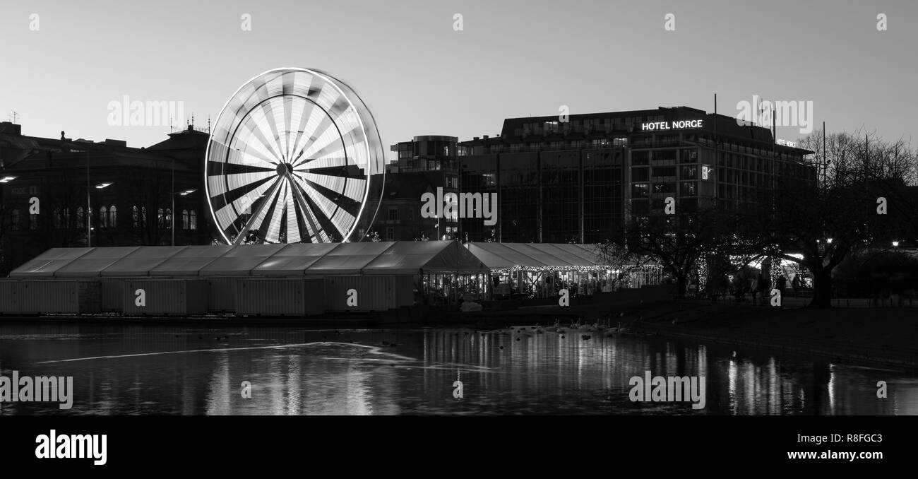 Christmas Market by Lille Lungegaardsvannet Lake in downtown Bergen, Norway. Ferris wheel rotating. Stock Photo