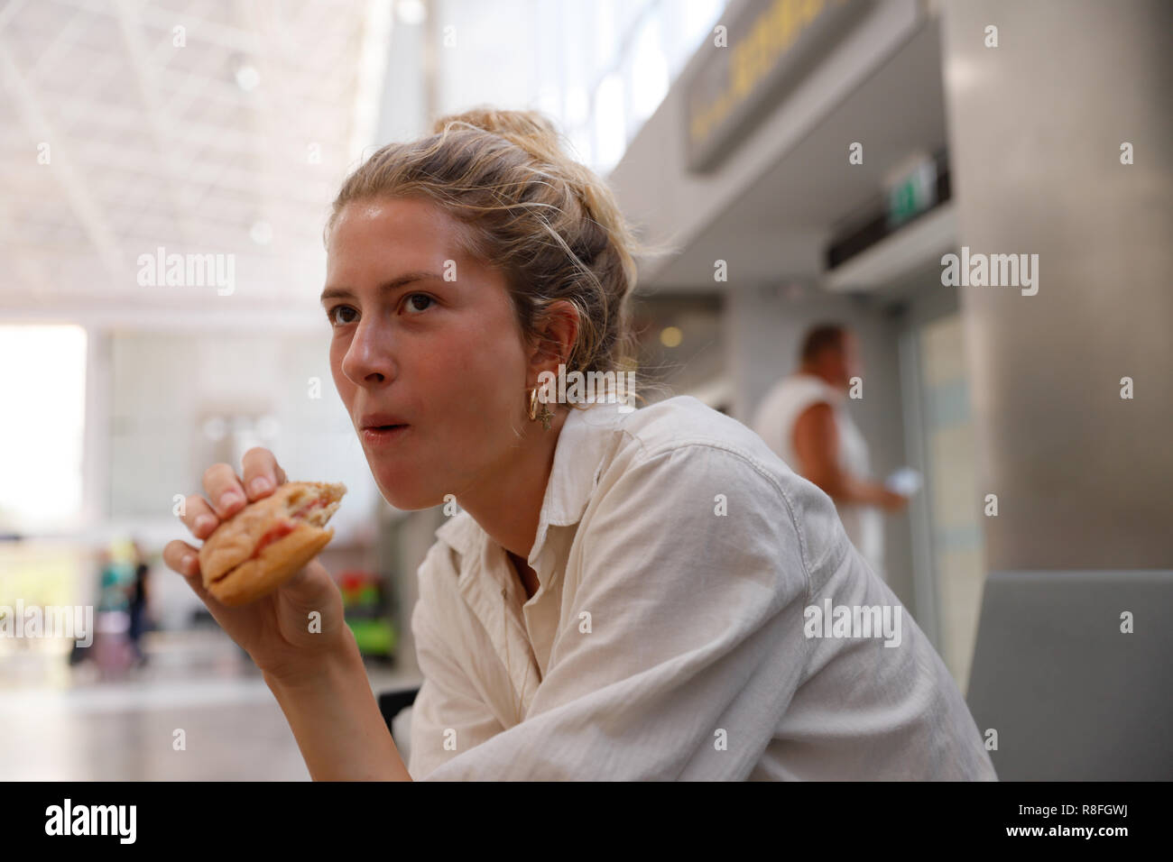 Young woman, authentic, natural, unplugged, waiting for her flight at the airport of Tenerife while eating a bun. - Stock Image