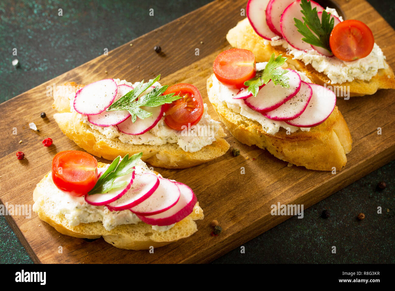 Antipasti snacks set for Wine. Brushetta or Crostini with Toasted Baguette,  Cheese, Radish and Tomatoes served on a rustic wooden board on a stone ta - Stock Image