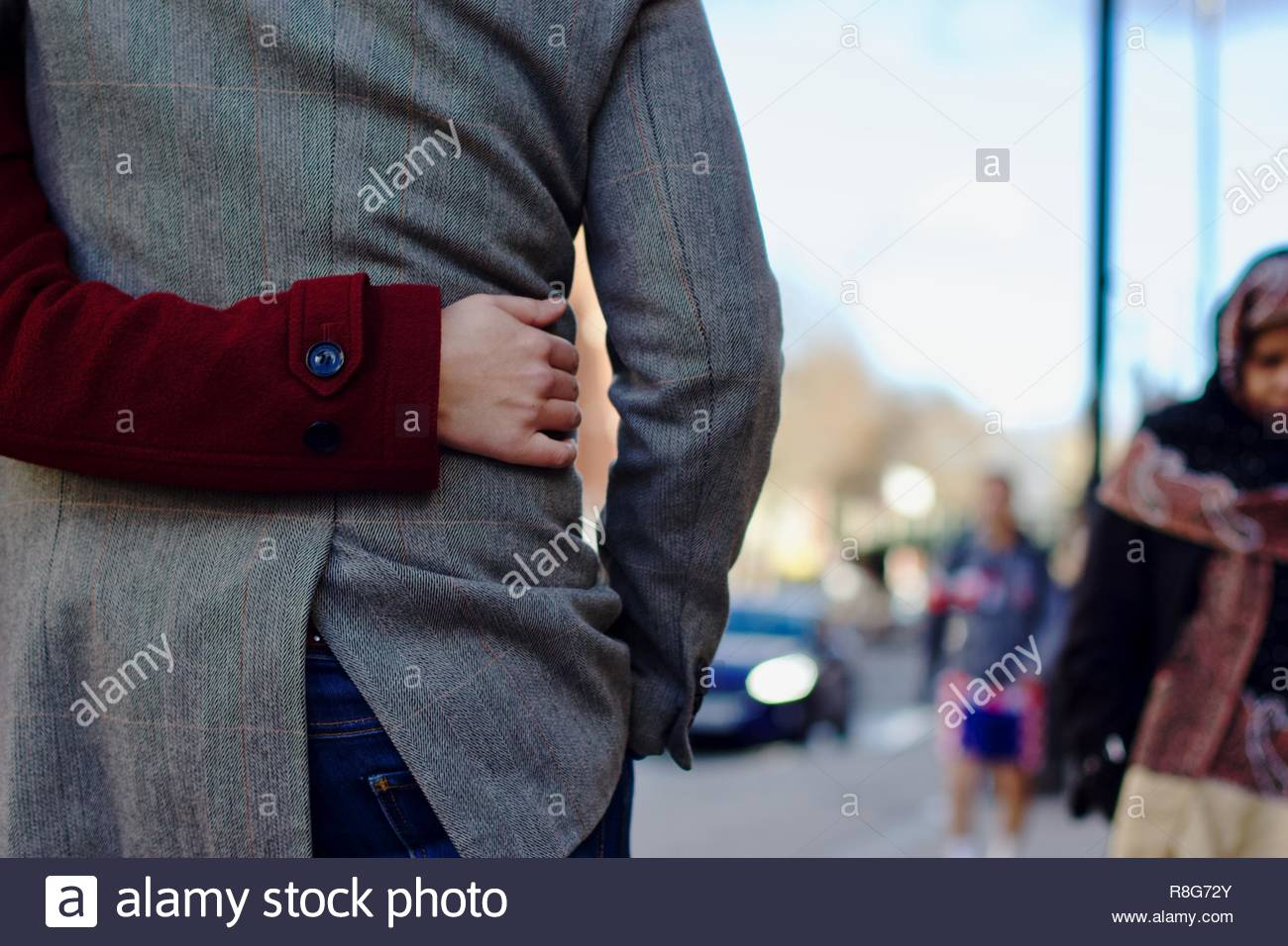 A woman in a red coat putting her arm around her partner's waist in embrace whilst walking down the street - Stock Image