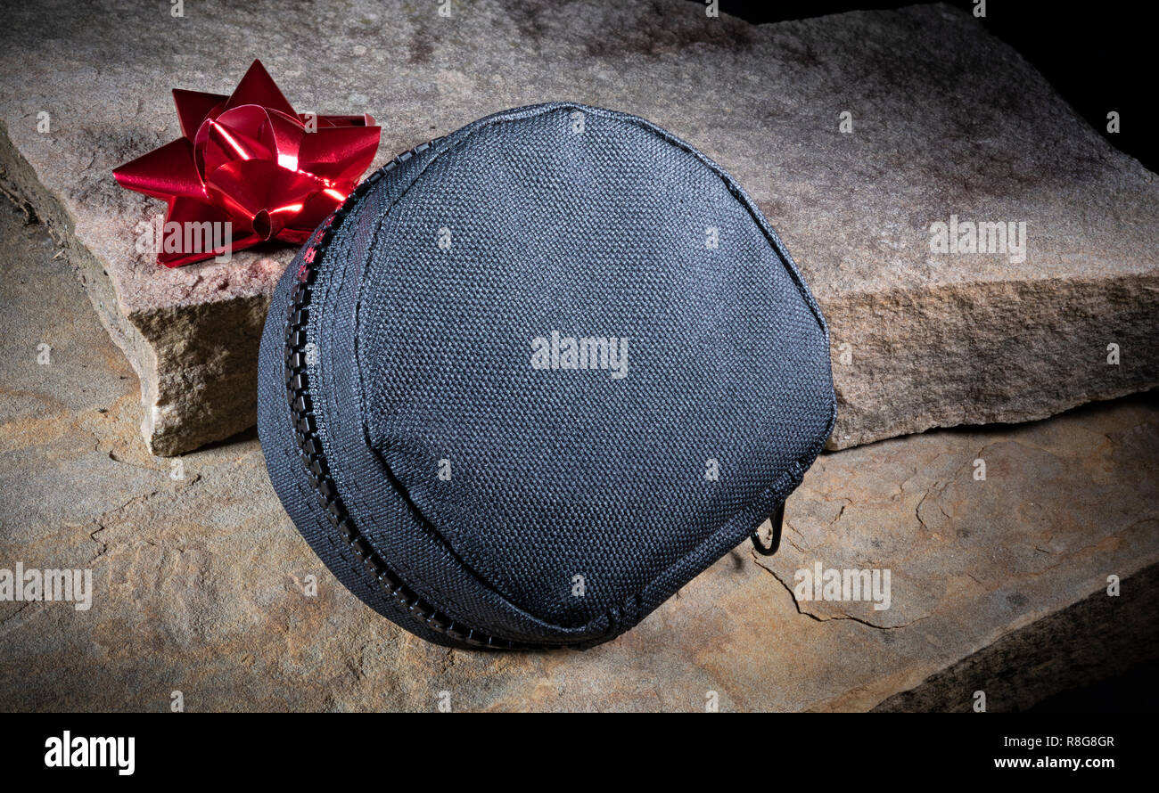 Red Christmas bow and zippered tactical bag on beige stones - Stock Image
