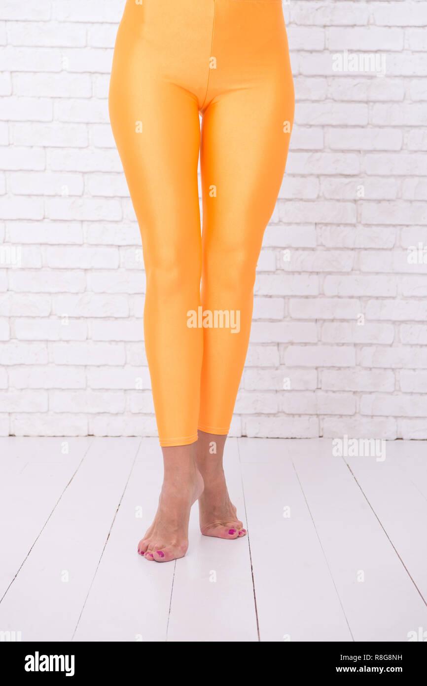 sport wear fashion. orange. practicing in ballet studio. woman in orange leggings on legs. dancing ballet position of feet. A Trendy Dance. Desire meets dance. Your Favourite Dancing Academy - Stock Image