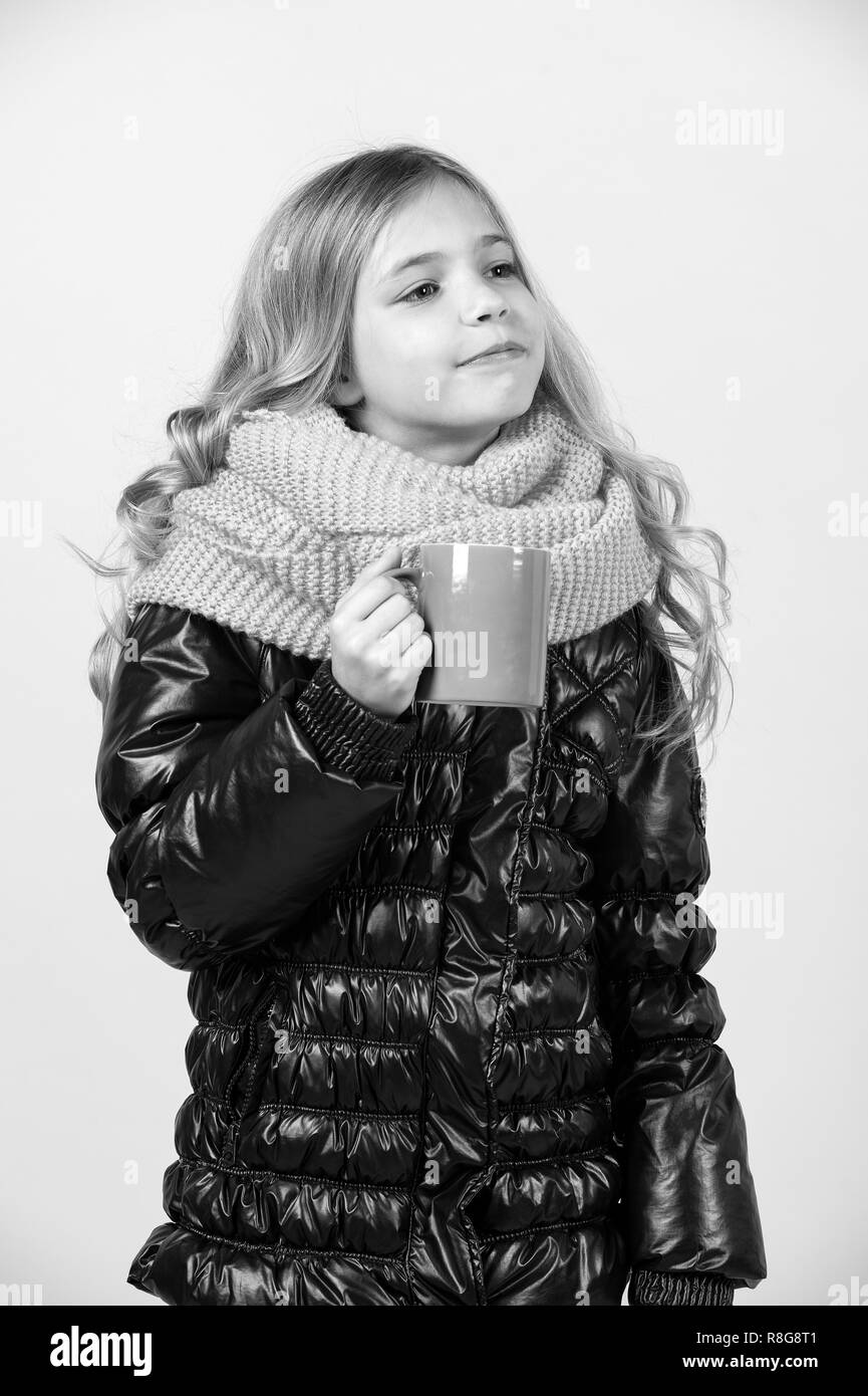 Hot drink in cold weather. Girl with blue cup on orange background. Autumn season relax concept. Child hold mug in black jacket and pink scarf. Tea or coffee break. - Stock Image