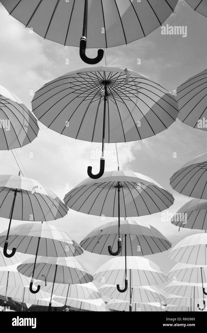 Outdoor art design and decor. Umbrellas float in sky on sunny day. Umbrella sky project installation. Holiday and festival celebration. Shade and protection. Stock Photo