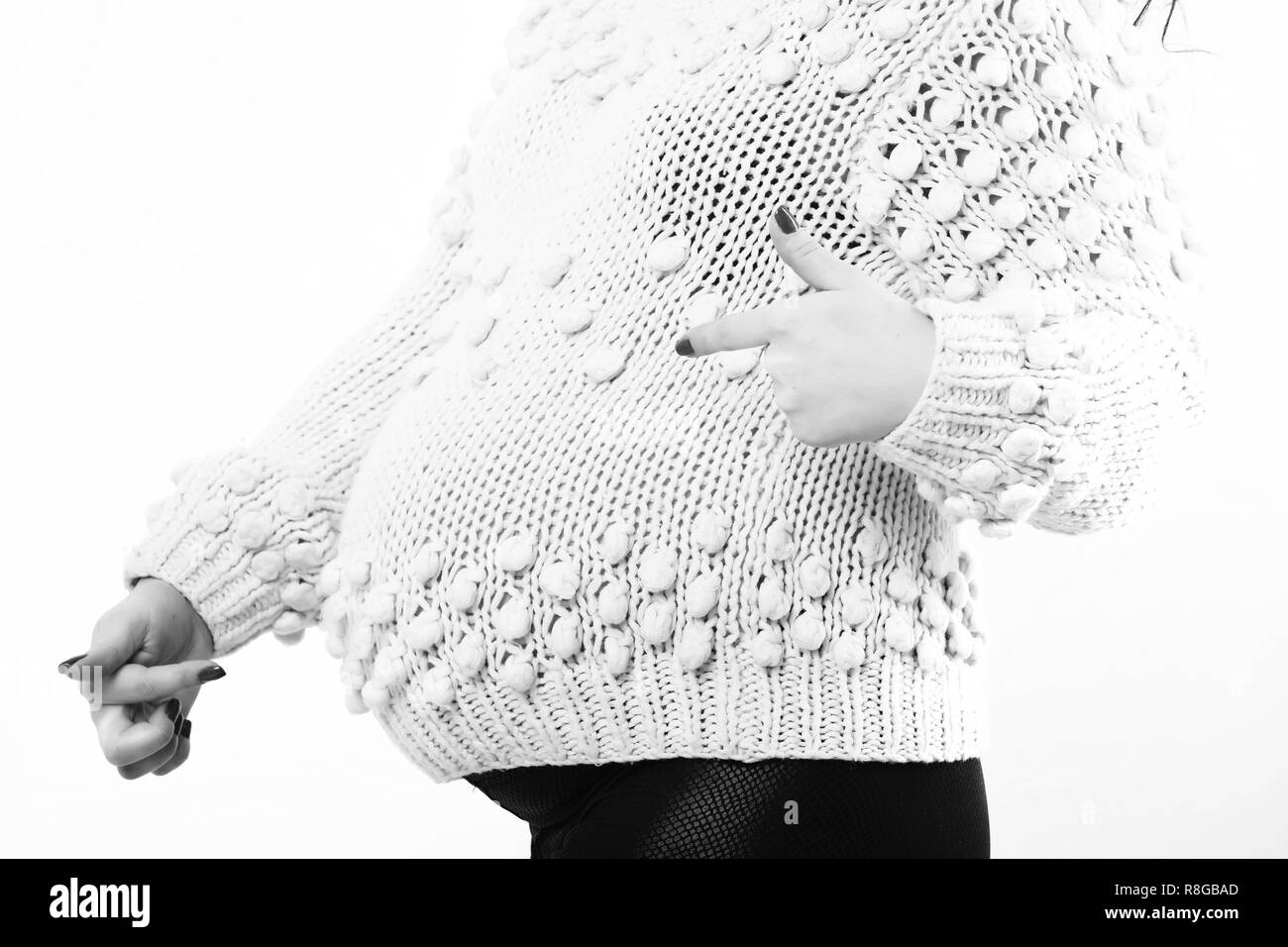 female hands of pregnant woman showing cool in beige knitted sweater isolated on white studio background - Stock Image