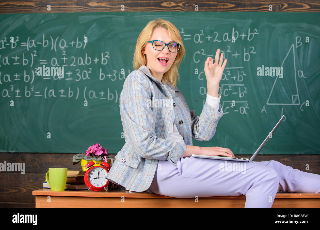 Incredible lecturer lady know how stay in touch modern generation. Influence non formal environment. Woman teacher hold laptop sit table classroom chalkboard background. Teacher of modern generation. - Stock Image