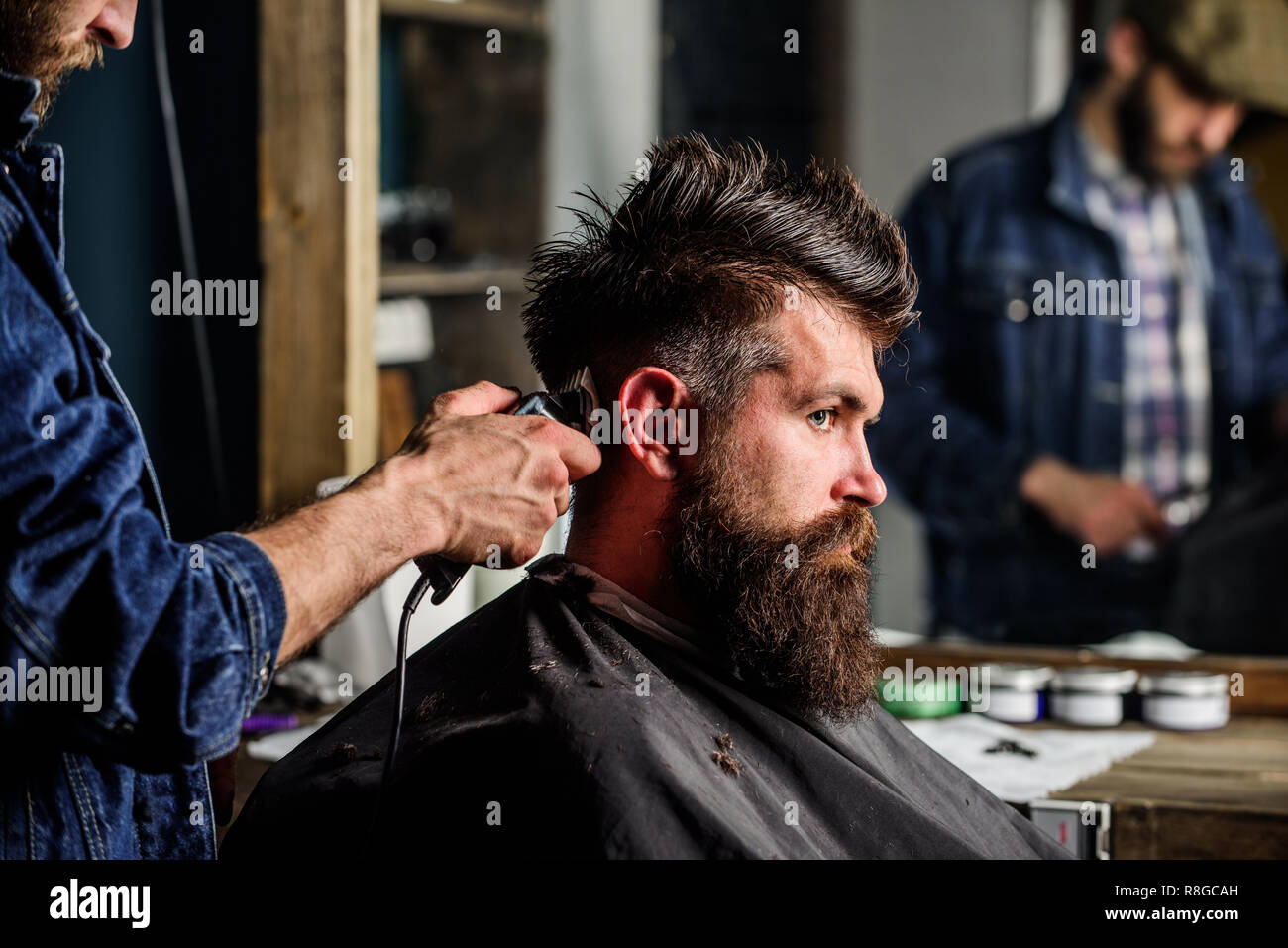 Barber styling hair of brutal bearded client with clipper. Barber with hair clipper works on hairstyle for bearded man barbershop background. Hipster lifestyle concept. Hipster client getting haircut. - Stock Image