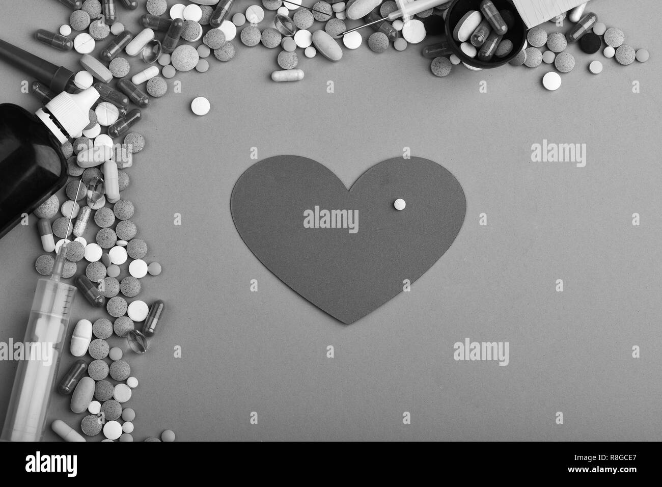 Medicine and love concept. Set of colorful pills scattered on green background, copy space. Drugs near syrup bottle, syringes, measuring spoon and heart in middle. Frame made of pills and capsules - Stock Image