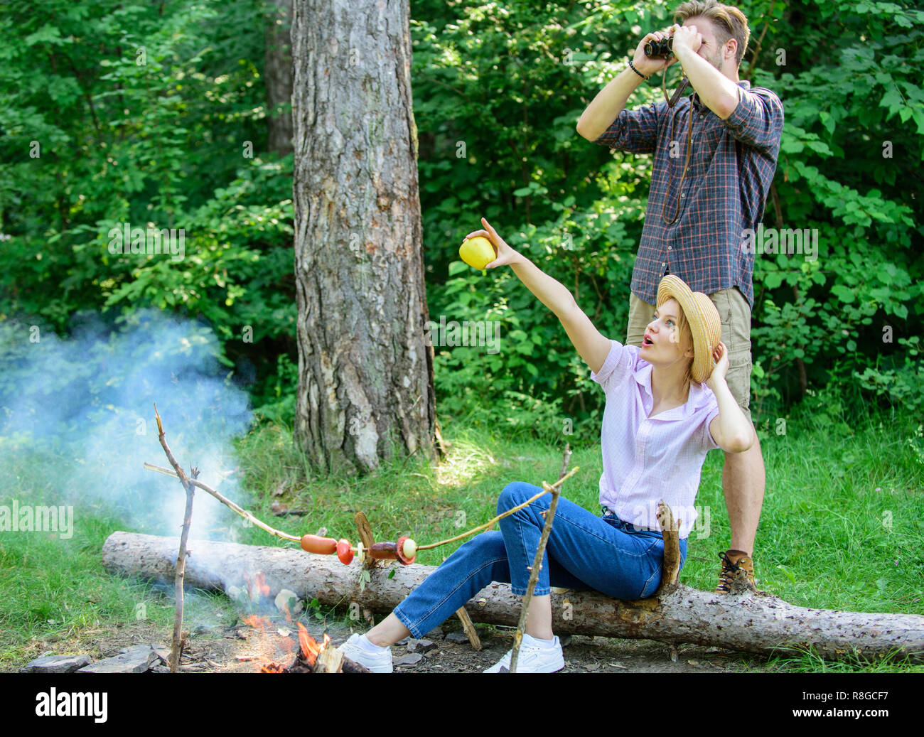 Couple enjoy hike in forest observing nature. Couple ornithologists expedition in forest. Observing nature concept. Ornithology interesting occupation. Woman and man looking binoculars near bonfire. - Stock Image