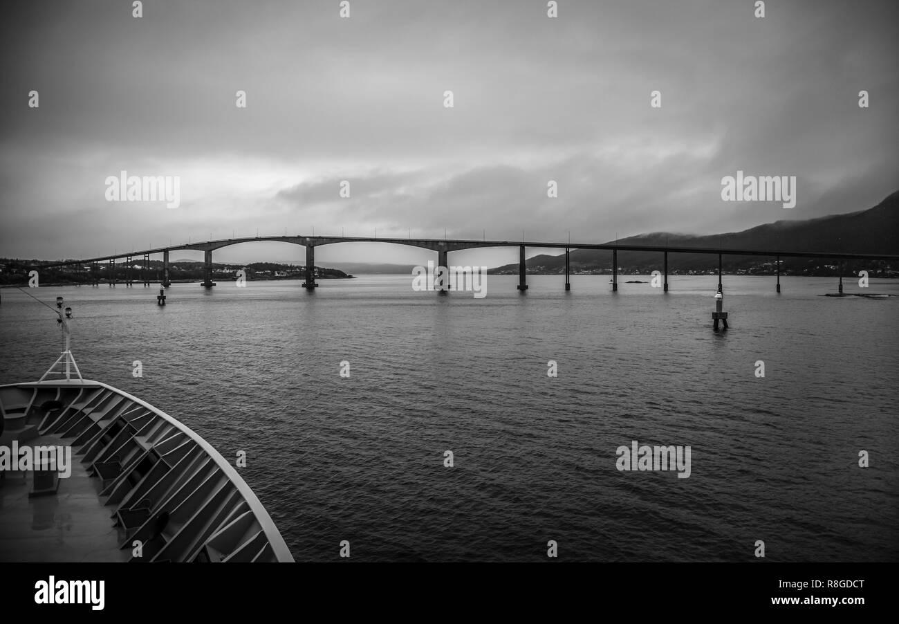 Fahrt mit dem Schiff unter einer Brücke in Finnsnes, Norwegen - Stock Image