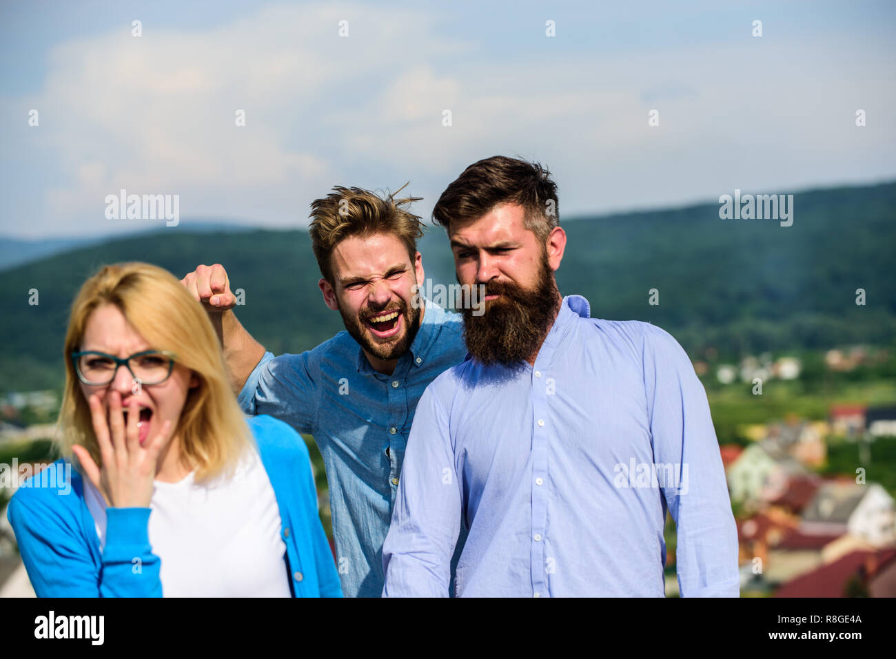 Man aggressive going to attack lover of his girlfriend. Boyfriend full of jealous looks suspiciously at couple. Jealous concept. Man found or detected girlfriend cheating him walking with another man. - Stock Image