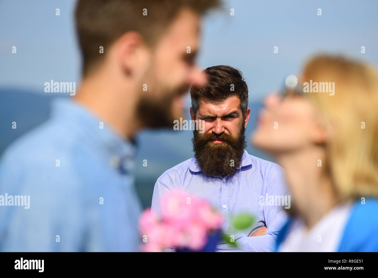 Lovers meeting outdoor flirt romance relations. Couple romantic date lover present bouquet flowers. Couple in love dating while jealous husband fixedly watching on background. Unrequited love concept. - Stock Image